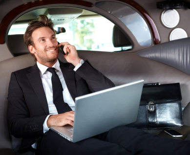 Smiling handsome businessman sitting in luxury limousine