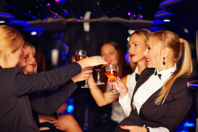 Beautiful happy women clinking glasses in limousine